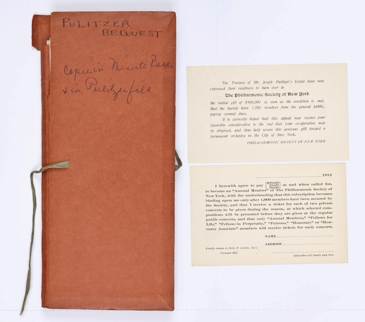 "Aged brown envelope labeled ""Pulitzer Bequest"" in handwritten ink, next to two small printed cards."