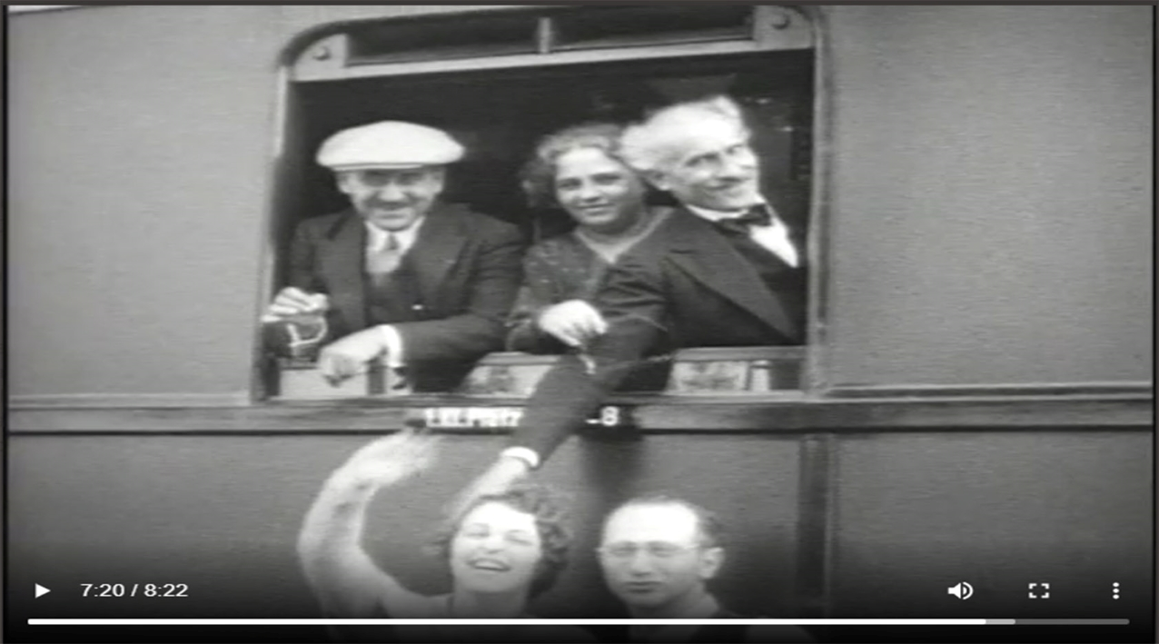 Toscanini, right, smirks and reaches out the window of a train to pat a woman's head. Other Philharmonic musicians and staff smile.