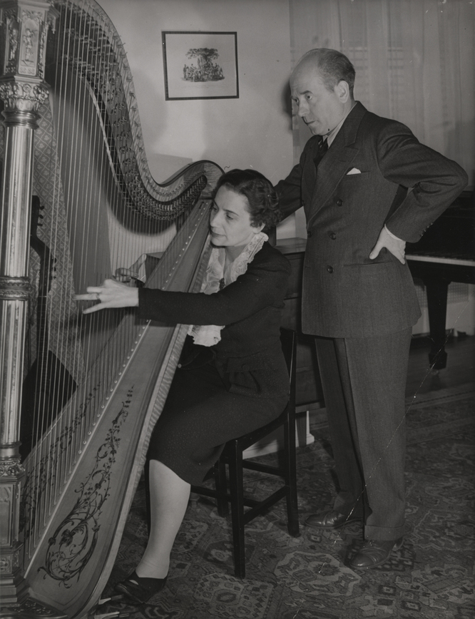 Photograph of Steffy Goldner seated playing harp with Eugene Ormandy standing behind her.